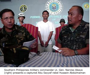 Southern Philippines military commander Lt. Gen. Narciso Abaya (right) presents a captured Abu Sayyaf rebel Hussein Abdulmaman