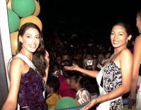 Sonia Raciti, MISS SOUTH AFRICA 1999, and Miriam Quiambao, MISS PHILIPPINES 1999, show off the crowd greeting them on their way to a reception at the home of Trinidad and Tobago's President Arthur Robinson on May 16, 1999.