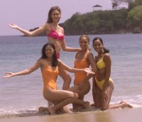 Miriam Quiambao, MISS PHILIPPINES 1999, Carolina Alfonso, MISS ECUADOR 1999, Glennis Knowles, MISS BAHAMAS 1999, and Jouraine Ricardo, MISS CURACAO 1999 play in the Tobago surf wearing their Oscar de le Renta swimsuits during filming for the 1999 Miss Universe Pageant.